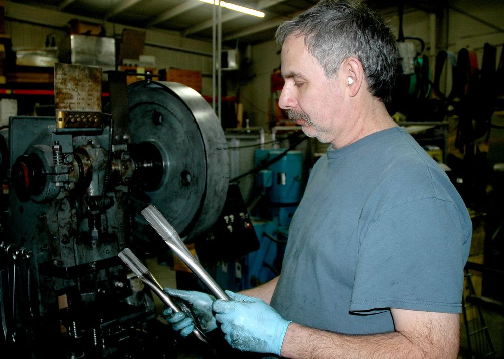Machinist examines bent and </br>flattened steel tubing
